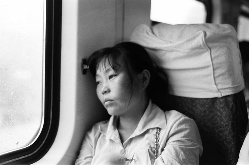 坐铁皮火车对面疲惫的妇女