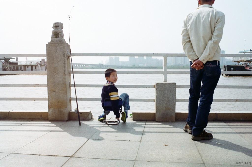 """他推开爸爸,不用他在一旁""""指手画脚""""。他要像江边每一个钓鱼的大人一样自己甩杆长钓。"""
