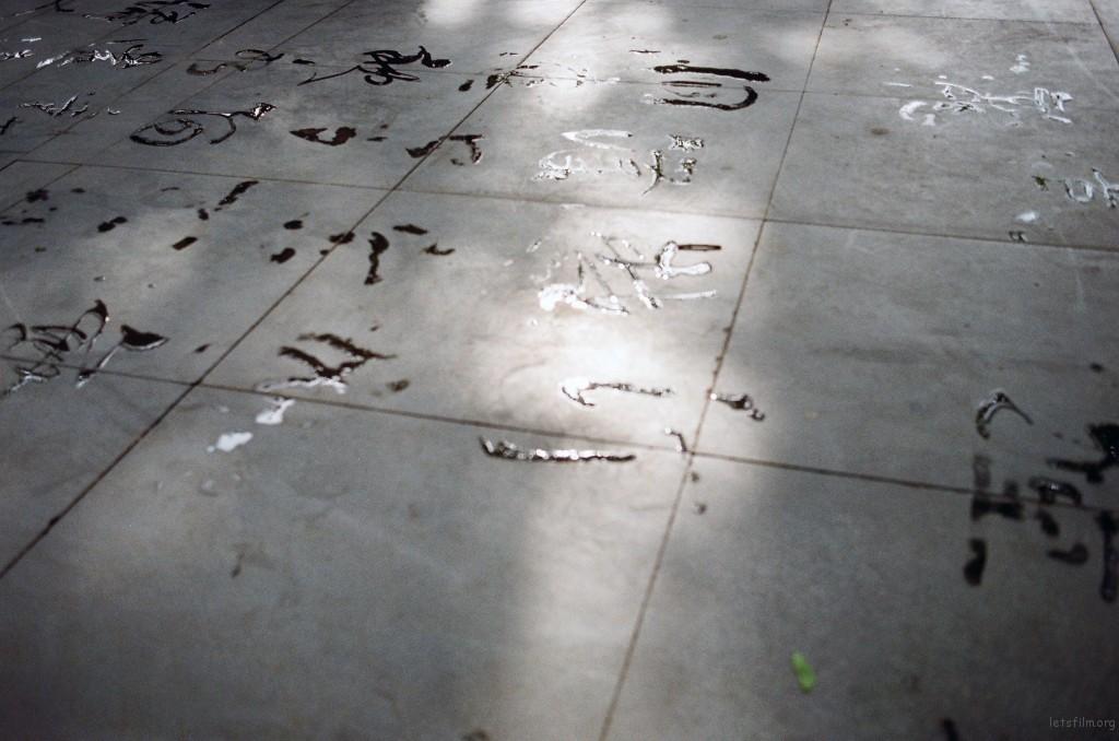 湖大老教授写的字。几个书法爱好老者几乎每天都会来练字。弯腰屈膝背挺直,斗大的毛笔直接在地上蘸水挥毫,很潇洒。