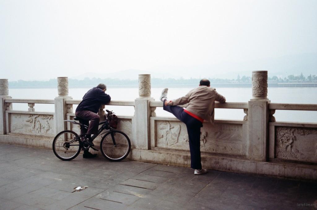 骑自行车的老人好奇压腿的老人在看什么,也停下车一起看。热闹的长沙人也总爱热闹。