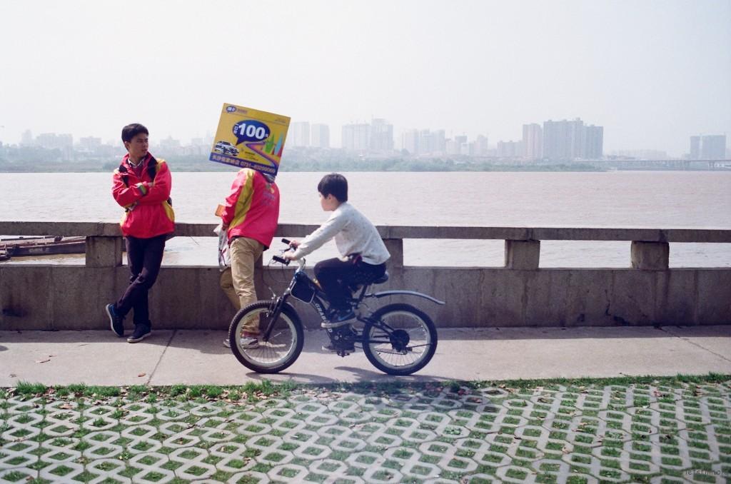 好天气让最优秀的员工都无法抵抗,两个人举着广告牌躲到江边来偷闲。