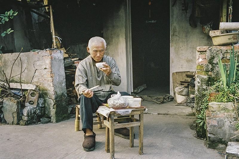 趁着天还未黑,一位独居老人在屋外解决晚饭。
