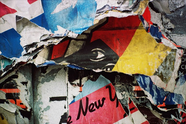 An abstract close-up of patterns formed by layers of torn posters with a depiction of a human eye at the centre, USA, circa 1970.