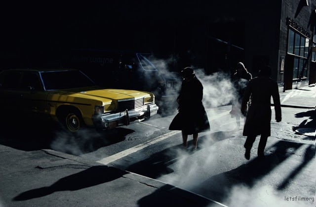 Pedestrians crossing a New York street in winter time cast long shadows, 1980.