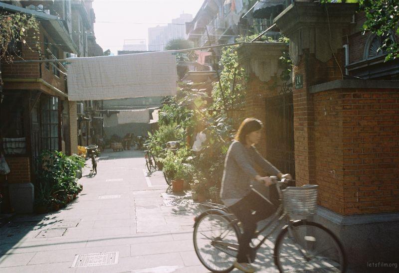 上海的老弄堂里 女人踩上单车准备去接放学的孩子