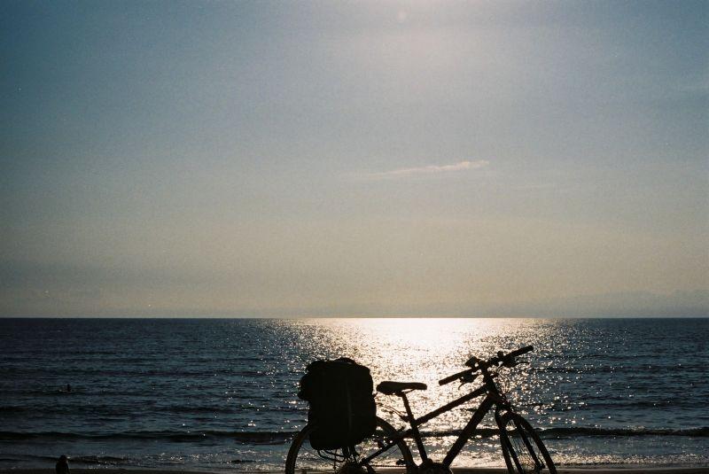 水族馆旁边的海,自行车旁边有人躺着在晒太阳 。