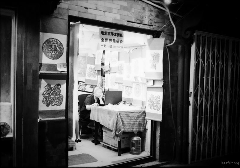 南锣鼓巷里面一位卖剪纸的老婆婆,周围熙熙攘攘,老婆婆自顾自在上网,完全置身度外的感觉。