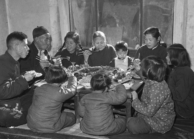 图为1953年春节,天津市汉沽区芦台王德铸(左一)一家人吃团圆饭。