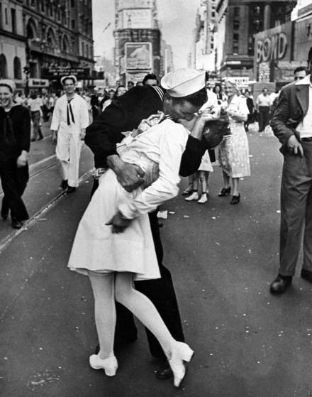 "Caption from the August 27, 1945, issue of LIFE. ""In the middle of New York's Times Square a white-clad girl clutches her purse and skirt as an uninhibited sailor plants his lips squarely on hers."""