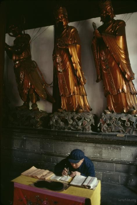 一位老人正在寺庙里抄写经文