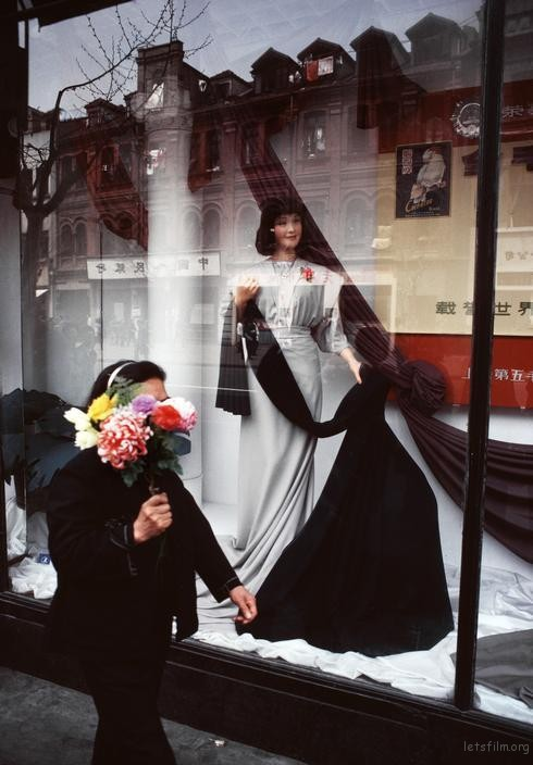 一名拿着花束的女子走过商店橱窗