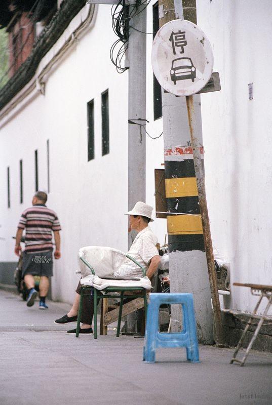 这是街边的一个老手艺理发师,他的摊位就固定在街边的这个地方。