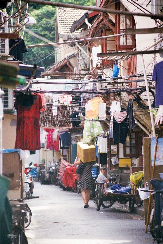 最开始只想拍一个老街的街景,中途忽然走进来一个扛着很重货物的女人,于是画面里有了故事,生动了许多。