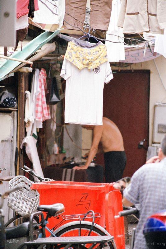 走在街道最里面,忽然发现一个在熨衣服的大爷,他的前景衣服和垃圾箱,和后面的形成了一个独特的,故事架构。