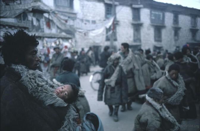 1981年,拉萨,大街上一位父亲用厚羊毛大衣裹着自己的孩子