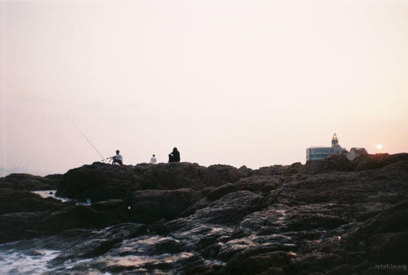 从小在内陆城市长大的旱鸭子。第一次去海边,岸上的路人真的非常有意思,没有一个人有重复的动作。拍了很多张,选了其中这一张。夕阳之下,各怀心事的三个人。