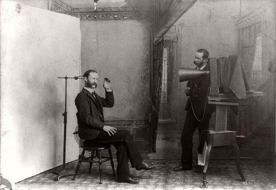 """19世纪的一家照相馆,这张照片可能还是一张分身照,扮演顾客和""""摄影师""""的是一个人。顾客脑后的就是固定头部的支架。"""